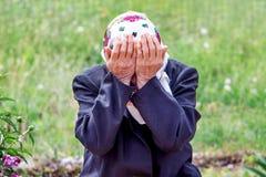 En äldre kvinna gråter och att täcka hennes framsida med henne händer symbol arkivbilder