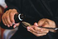 En äldre kvinna häller medicin i en sked Royaltyfri Fotografi