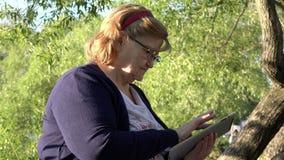 En äldre kvinna i exponeringsglas framkallar informationsteknik i den elektroniska minnestavlan som studerar försiktigt hans appa stock video
