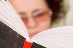 En äldre kvinna i oculature läste en book_ fotografering för bildbyråer