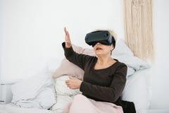 En äldre kvinna i virtuell verklighetexponeringsglas En äldre person som använder modern teknologi royaltyfri foto