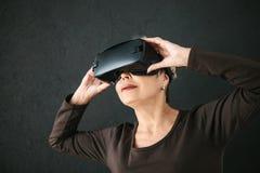 En äldre kvinna i virtuell verklighetexponeringsglas En äldre person som använder modern teknologi arkivfoton
