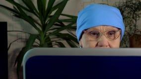 En äldre kvinna med exponeringsglas använder en bärbar dator stock video