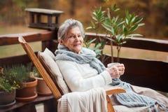 En äldre kvinna med en kopp som utomhus sitter på en terrass på en solig dag i höst fotografering för bildbyråer