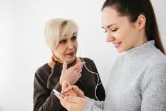 En äldre kvinna och en ung flicka lyssnar till musik tillsammans Kommunikation mellan folk av olika utvecklingar Arkivfoto
