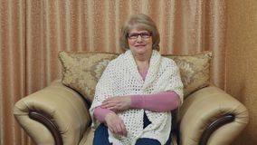 En äldre kvinna sitter i en bekväm stol och ler Lycklig kvinna som hemma kopplar av i en läderstol lager videofilmer