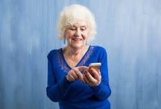 En äldre kvinna som använder smartphonen arkivbild