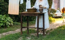 En äldre kvinna tvättar kläder i trädgården i vita tappningkläder livstid för kattunge för kattlandsko kläder torkar på ett rep fotografering för bildbyråer