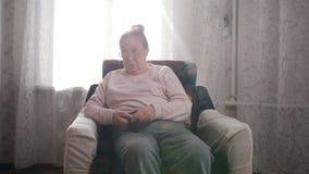 En äldre kvinna tycker om hennes hobbysammanträde i en stol och handarbete på bakgrunden av fönstret arkivbild