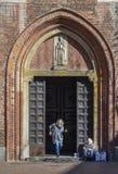 En äldre kvinnatiggare som verkar att vara en Roma Gypsie som framme tigger av en kyrka i Milan royaltyfri fotografi