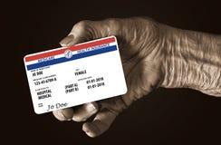 En äldre kvinnlig hand rymmer ett falskt enigt kort för delstatsregeringMedicare sjukförsäkring Det är ett generiskt kort royaltyfria foton