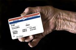 En äldre kvinnlig hand rymmer ett falskt enigt kort för delstatsregeringMedicare sjukförsäkring Det är ett generiskt kort royaltyfri bild