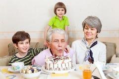 En äldre man blåser stearinljus på kakan Arkivbild