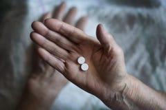 En äldre man dricker en medicin En pensionär tar en preventivpillerläkare arkivbild