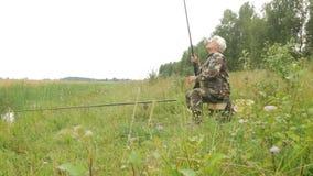 En äldre man fiskar på en liten flod i sommaren Använder en metspö och avmaskar Skog och högt grönt gräs lager videofilmer