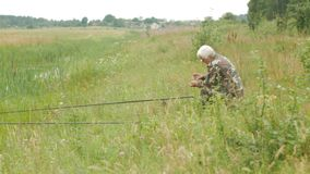 En äldre man fiskar på en liten flod i sommaren Använder en metspö och avmaskar Skog och högt grönt gräs arkivfilmer