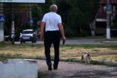 En äldre man går med en hund på vägen royaltyfria foton