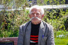 En äldre man i ett omslag med en härlig stor grå krullad mustasch på den Yerevan gatan arkivfoto