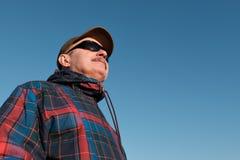 En äldre man i solglasögon och en baseballmössa ser bort arkivbild