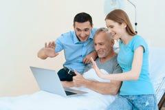 En äldre man ligger i ett sjukhusrum på en säng Han ses av en man med en kvinna royaltyfria bilder