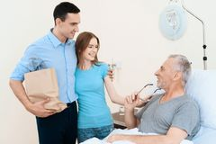 En äldre man ligger i ett sjukhusrum på en säng Han ses av en man med en kvinna De står bredvid hans brits royaltyfria bilder