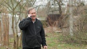 En äldre man med en mustasch röker och talar på telefonen i gatan De gamla husen är bak oss Svarten arkivfilmer
