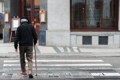 En äldre man med en gå pinne går långsamt över en övergångsställe i mitt av en stad bara arkivbild