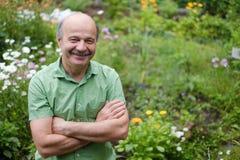 En äldre man med en mustasch och en skallig fläck i en grön T-tröja står bland blommor i sommarträdgården, armar royaltyfri bild
