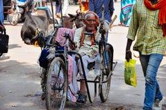 En äldre man rider hans cirkulering i Varanasi, Indien arkivfoto