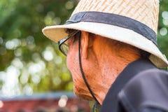 En äldre man som bär en vit hatt, förbereder sig att bruka fotografering för bildbyråer