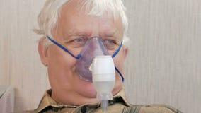 En äldre man som rymmer en maskering från en inhalator hemmastadd Behandlar inflammation av flygbolagen via nebulizeren förhindra lager videofilmer