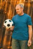 En äldre man som rymmer en fotbollboll royaltyfri fotografi