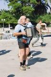 En äldre man som spelar den dragspels- yttersidan på stranden av ön royaltyfria bilder