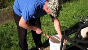 En äldre man tänder en fyrpanna för grillfest i en härlig borggård stock video