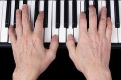 En äldre pensionerad man spelar en gammal melodi på tangentbordet av th Royaltyfri Foto
