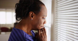 En äldre svart kvinna ser sorgset ut hennes fönster fotografering för bildbyråer