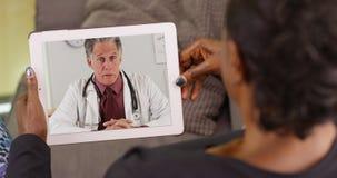 En äldre svart kvinna som talar till hennes doktor via video pratstund fotografering för bildbyråer