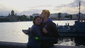 En älska parman och kvinna, ställning på stranden, nära floden i staden och kyssen långsam rörelse 1920x1080 Full HD lager videofilmer