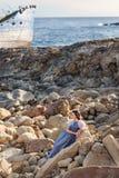 En älskvärd ung kvinna sitter behagfullt elegantly på stenarna som väntar med ett övergett fartyg på bakgrunden Arkivbilder