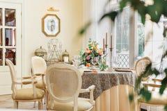En äta middag tabell och bekväma fåtöljer i ett modernt hus med en ljus matsal Fotografering för Bildbyråer