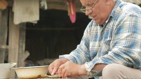 En åldringfiskare gör ren en liten fisk Förbereder en maträtt för familjen arkivfilmer