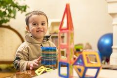 En 2 år pojke spelar vid en magnetisk konstruktör Intellektuella leksaker Lycklig le pojke som spelar med den magnetiska konstruk Arkivfoto