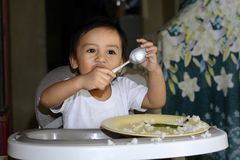En 1 årig asiat behandla som ett barn pojken som lär att äta vid honom vid skeden som är smutsig behandla som ett barn på, äta mi royaltyfria bilder