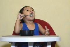 En 1 årig asiat behandla som ett barn pojken som lär att äta vid honom vid skeden som är smutsig behandla som ett barn på, äta mi Arkivbild
