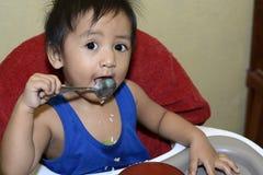 En 1 årig asiat behandla som ett barn pojken som lär att äta vid honom vid skeden som är smutsig behandla som ett barn på, äta mi Royaltyfria Foton