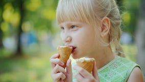 En 6-årig flicka åt samtidigt två kottar av läcker glass Sommarferier, vilar i parkera royaltyfria bilder