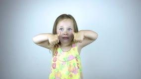 En årig flicka för barn tre har gyckel och hoppar framme av kameran stock video