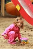 En årig gullig lockig flicka i rosa sportar passar att spela och framställning av sandslottar på lekplatsen Royaltyfri Bild