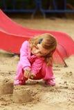 En årig gullig lockig flicka i rosa sportar passar att spela och framställning av sandslottar på lekplatsen Arkivfoton