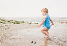 En årig pojke spelar på stranden arkivfoton